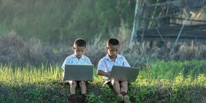 2 Kinder mit Laptop in freier Natur